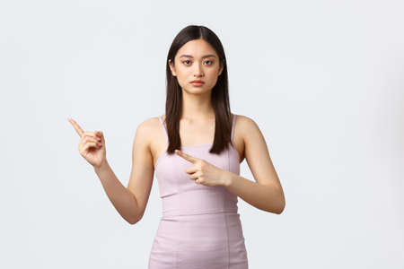 Celebration, beauty and glamour concept. Serious-looking asian woman in elegant evening dress, showing where party, way to holiday event, pointing fingers left, white background