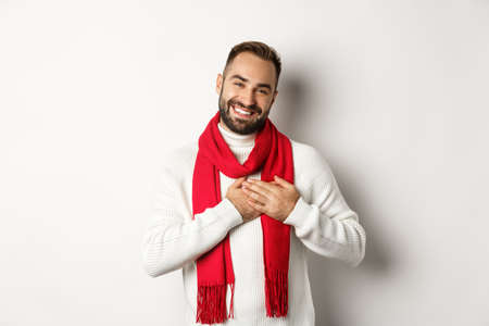 Christmas holidays and celebration concept. Handsome man thanking for new year gifts, holding hands on heart and smiling grateful, standing against white background Foto de archivo