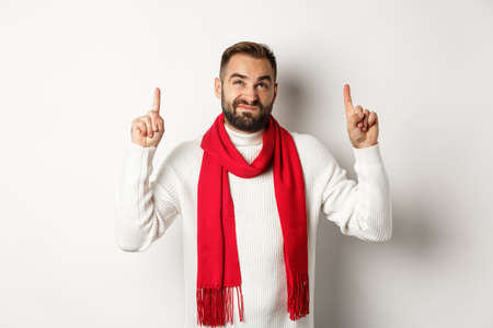 Christmas shopping and winter holidays concept. Displeased bearded guy complaining, pointing finger up and looking reluctant, standing over white background