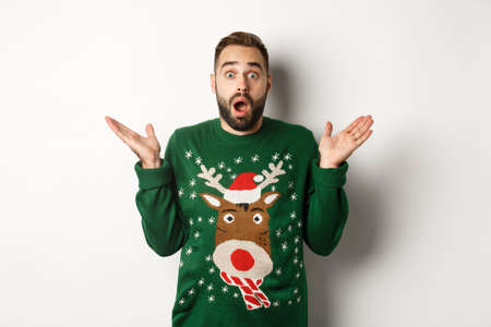 New Year party and winter holidays concept. Surprised bearded guy gasping amazed, standing in Christmas sweater, white background
