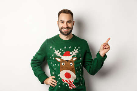 Winter holidays and christmas. Handsome bearded adult man pointing finger right at promo banner, standing in funny sweater against white background Stock Photo
