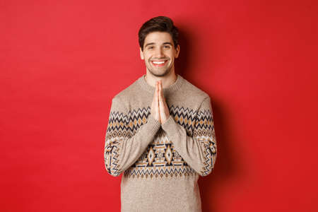 Image of happy and cute man in christmas sweater, asking for favour, holding hands together, smiling and saying thank you, feeling grateful, standing over red background