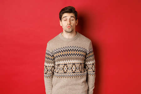 Image of handsome man in christmas sweater pucker lips and close eyes, waiting for kiss under mistletoe, standing over red background