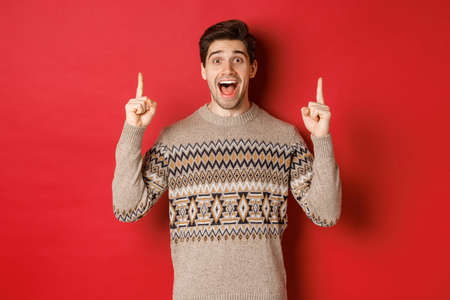 Image of handsome excited man, feeling happy about christmas holidays, pointing fingers up and looking cheerful, showing advertisement, standing in sweater over red background