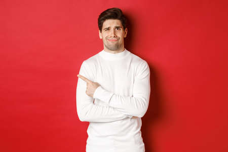 Concept of winter holidays, christmas and lifestyle. Image of skeptical young man in white sweater, dont like something, pointing finger left and looking with dismay, standing over red background