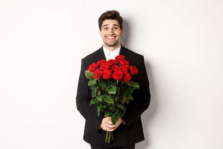 Image of handsome man in black suit, holding bouquet of roses and smiling, standing against white background