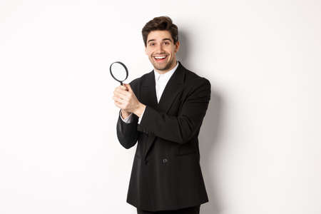 Handsome businessman in black suit, holding magnifying glass and smiling, looking for you, standing against white background