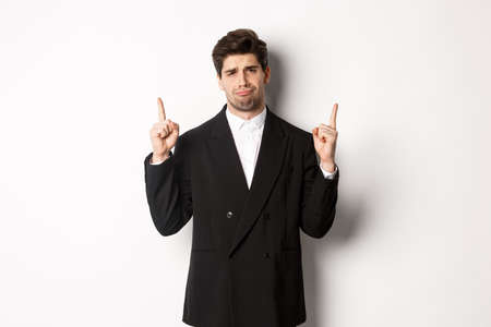 Portrait of reluctant and sad handsome man, complaining and pointing fingers up at something bad, looking jealous, standing over white background