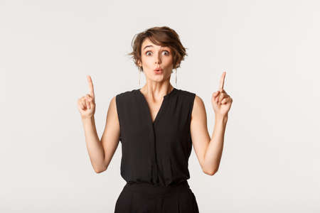 Image of surprised attractive woman looking impressed, pointing fingers up Banque d'images