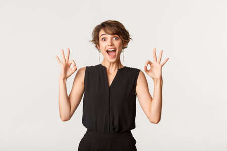 Amazed and impressed young woman showing okay gestures with fascinated expression, recommend product over white background