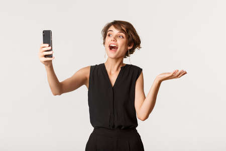 Attractive fashionable woman having video call, demonstrating something on mobile phone camera, standing white background Banque d'images