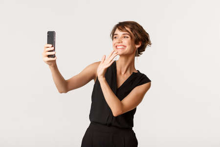 Happy gorgeous female having video call, waving hand at smartphone camera and smiling, standing white background