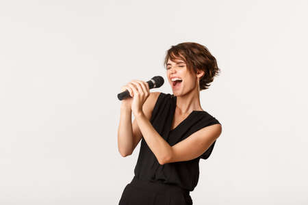 Carefree attractive girl singing in microphone, performing, have fun at karaoke, standing over white background