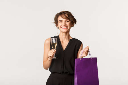 Cheerful attractive woman drinking glass of champagne and holding bag with gift, attend birthday party, standing over white background