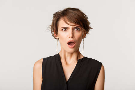 Close-up of shocked and disappointed woman frowning, drop jaw and stare frustrated, standing over white background Banque d'images
