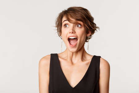 Close-up of excited, amazed young woman drop jaw and looking left, standing over white background Banque d'images