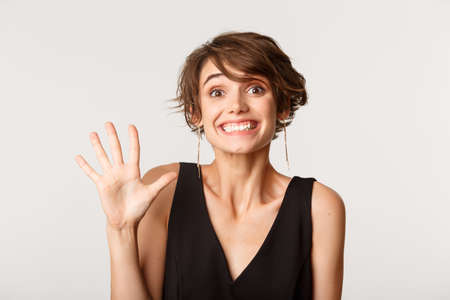 Close-up of pretty brunette girl smiling, showing number five, standing over white background Banque d'images