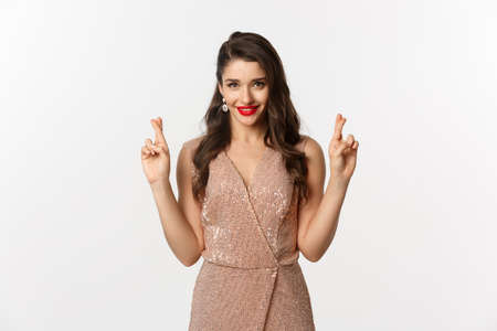 Concept of casino, celebration and party. Hopeful beautiful woman making a wish, cross fingers for good luck and looking confident, white background