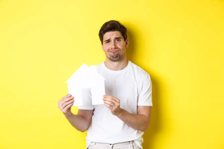 Real estate concept. Displeased young man showing paper house model and grimacing upset, standing over yellow background