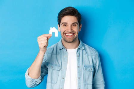 Real estate concept. Young handsome man smiling, showing small paper house mockup, searching for apartment, standing over blue background