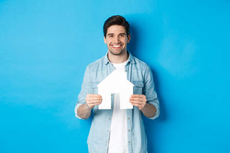 Insurance, mortgage and real estate concept. Smiling young man holding house model, searching apartment for rent, standing against blue background