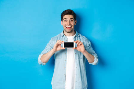 Amazed smiling man showing smartphone screen, internet promo offer, standing against blue background