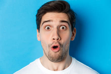 Headshot of surprised man gasping wondered, saying wow and looking amazed at camera, standing over blue background