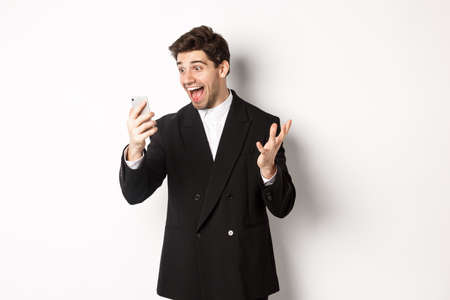 Portrait of happy smiling man in black suit, looking at smartphone screen with relieved and cheerful face, standing against white background