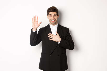 Image of handsome smiling guy telling the truth, raising on arm to promise something, standing over white background in black suit