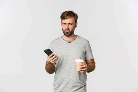 Image of disappointed frowning guy in gray t-shirt, drinking takeaway coffee and holding mobile phone, standing over white background Stock Photo
