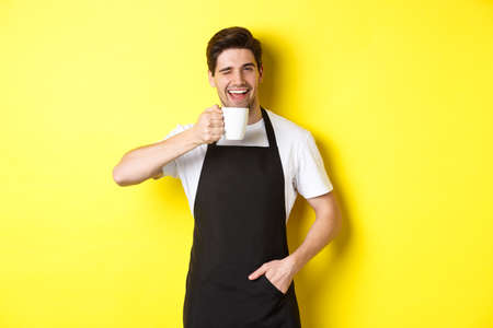 Handsome barista drinking cup of coffee and winking, inviting to cafe, standing over yellow background