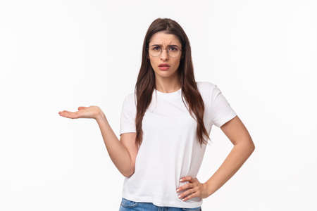 So what. Portrait of careless and unbothered, arrogant brunette woman in t-shirt, raise hand in dismay shrugging and stare with scorn or disdain camera, cant understand why person talking her Reklamní fotografie