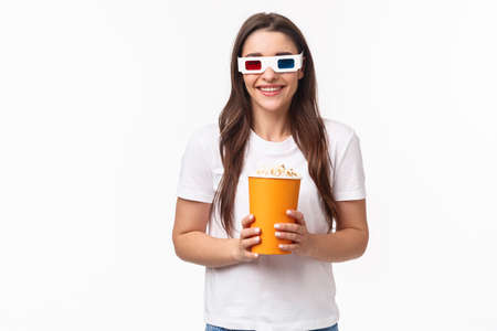 Entertainment, fun and holidays concept. Portrait of happy, joyful young girl enjoying watching awesome movie, premier night, wearing 3d glasses, smiling, eating popcorn, attend cinema