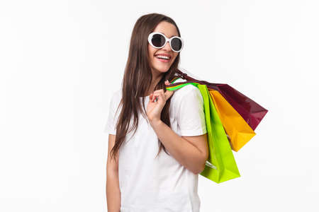 Shopping, leisure and lifestyle concept. Happy, joyful young feminine woman walking in store, buying new clothes and summer bikini, look back with smiling pleased look, hold bags on shoulder 免版税图像