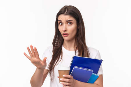 Education, university and studying concept. Wow come down, slow for minute. Close-up portrait of freaked-out shocked young female student saying stop, chill gesture, look concerned hold notebook
