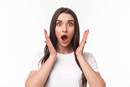What an amazing news. Surprised and astonished, excited young woman react to something awesome happened, gasping, open mouth and raise hands near face, staring camera, white background