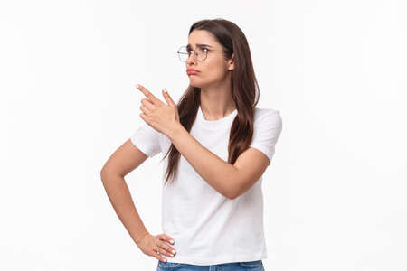 Waist-up portrait of pity or jealous young brunette female student missed great opportunity, feel regret and uneasy emotion, sulking grieving pointing and looking upper left corner Stock Photo