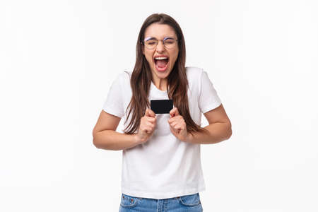 Portrait of excited female shopaholic cant wait to waste all money on her bank account, got new credit card, screaming from excitement and thrill, happy to shopping her favorite online store