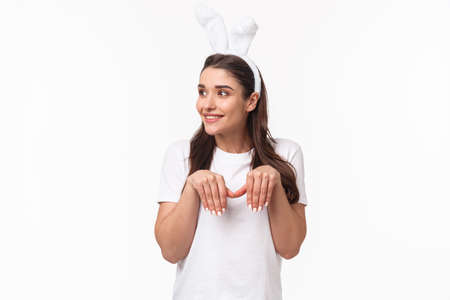 Portrait of funny and cute, playful adult girl in t-shirt and rabbit ears, look away with amused happy face, imitating bunny with paws and silly grin, look away, standing white background