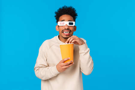 So scary. Trembling and terrified african-american hipster guy watching horror movie, frightening scene in film 3d glasses, holding paper box and eating popcron, standing tensed, blue background