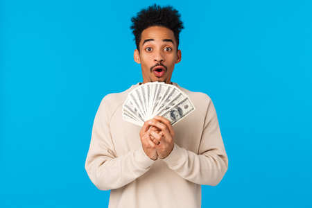 Lottery, sport bet and finance concept. Amazed and startled happy african-american guy got lots of cash, winning prize, holding big money and smiling, gasping astonished, blue background Imagens