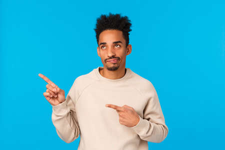 Skeptical and disappointed handsome stylish african-american modern guy in white sweater, smirk and staring with judgement and dislike at something lame, pointing upper left corner, blue background
