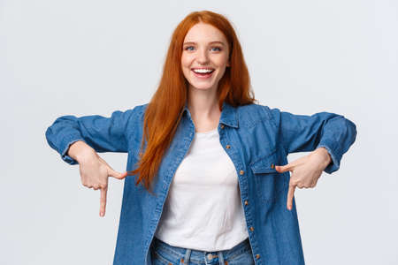 Must have, check this out. Waist-up portrait alluring, friendly redhead woman showing you good promo banner, review product, blogger indicate down, bottomg advertisement, white background
