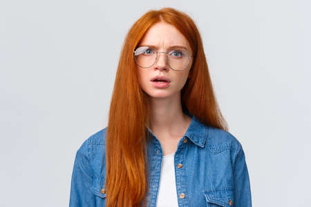 Confused and displeased, unsure redhead girl in glasses having conversation, talking look frustrated and slightly unconvinced, have doubts standing white background frowning