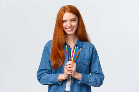 Time to brighten life. Attractive confident charismatic redhead girl in denim shirt, looking camera with pleased smile, holding colored pencils, standing white background drawing, attend courses