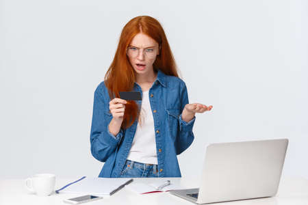 Wtf going on. Troubled and frustrated young girl trying pay for order, looking bothered and disturbed credit card, shrugging raise hand in dismay, dont know why payment cancelled, stand near laptop