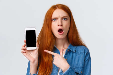 Close-up portrait angry and pissed-off redhead girl showing photos from social media ex-boyfriend complaining to friend, pointing finger smartphone display and frowning upset, white background Stockfoto