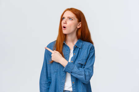 Perplexed and indecisive redhead cute girl cant understand wtf is that, pointing looking upper left corner with confused expression, dont know and asking question, standing white background