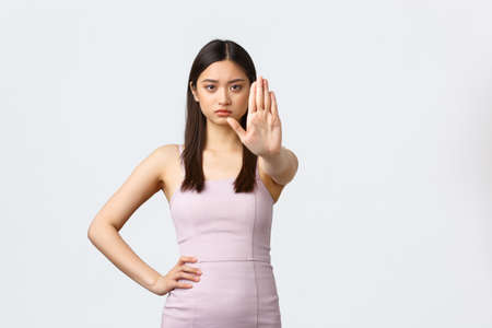Luxury women, party and holidays concept. Serious determined asian woman in evening dress telling to stop, say enough or no, frowning and extend hand in prohibition gesture, white background