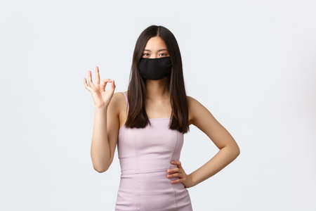 Covid-19, social distancing quarantine and leisure concept. Confident good-looking asian woman assure and guarantee safety of event celebration during coronavirus, wear protective face mask and dress